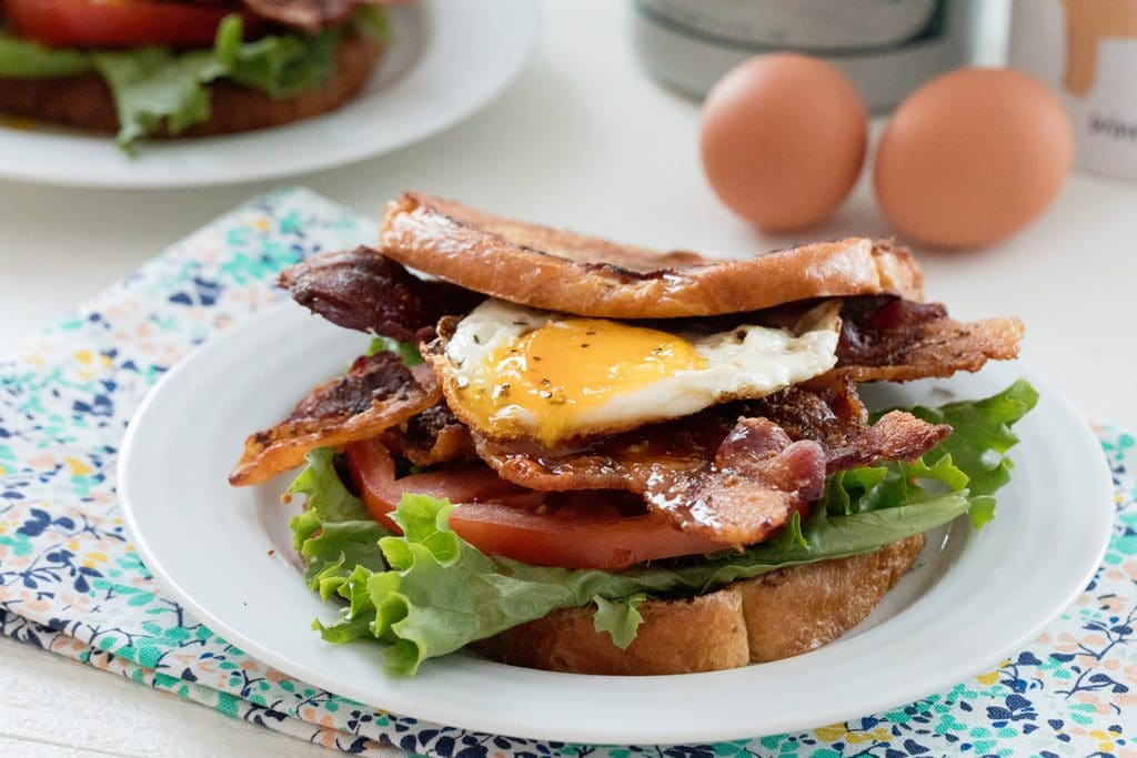 Landscape head-on view of a french toast BLT with eggs and maple syrup in background