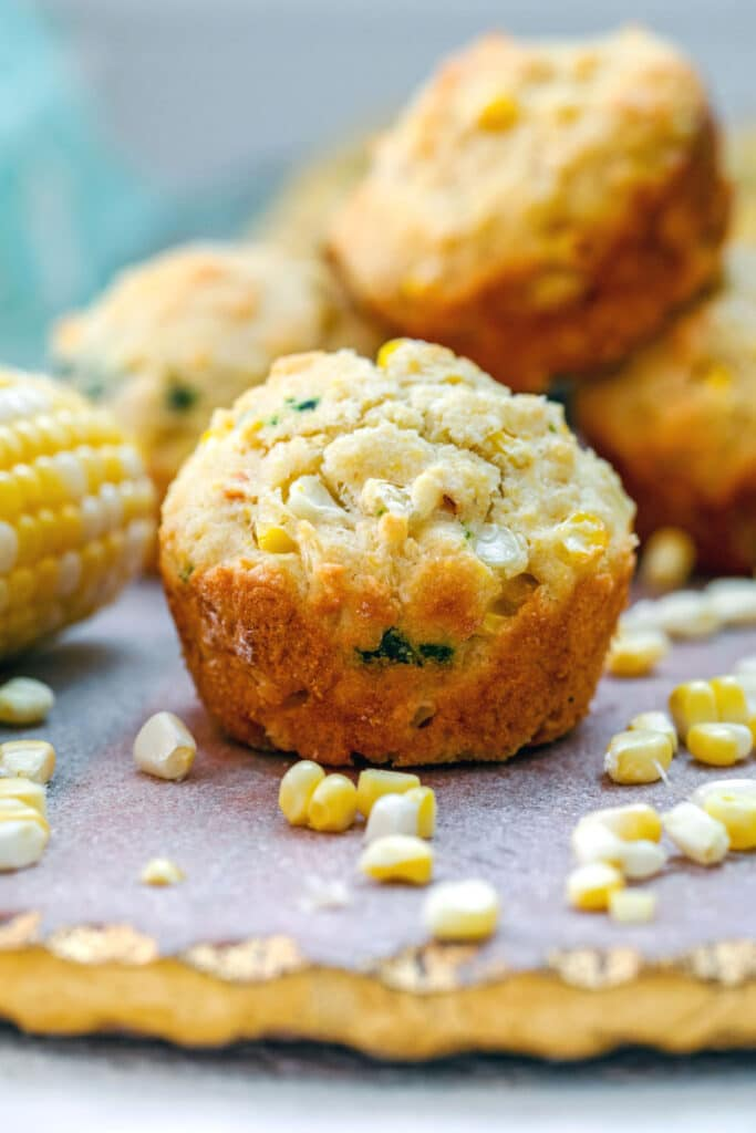 Head-on view of a fresh corn muffin surrounded by corn kernels and corn on the cob with more muffins in background