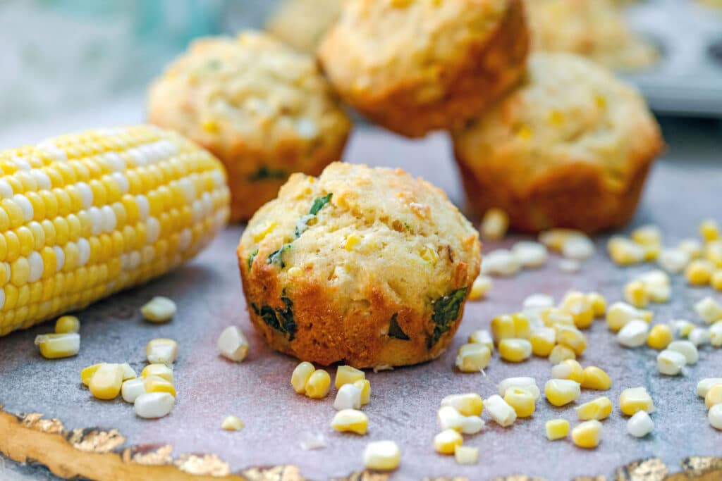 Landscape view of corn muffins with corn kernels, cobs, and more muffins all around