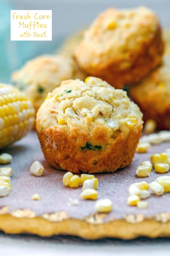 Head-on view of a fresh corn muffin surrounded by corn kernels and corn on the cob with more muffins in background and recipe title at top