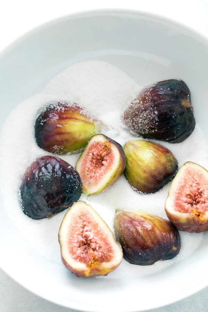 Overhead view of a bowl of granulated sugar with halved fresh figs in it