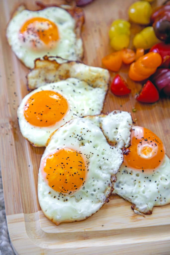 Fried eggs on wooden cutting board
