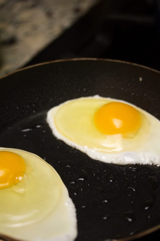 Overhead view of eggs frying in a skillet