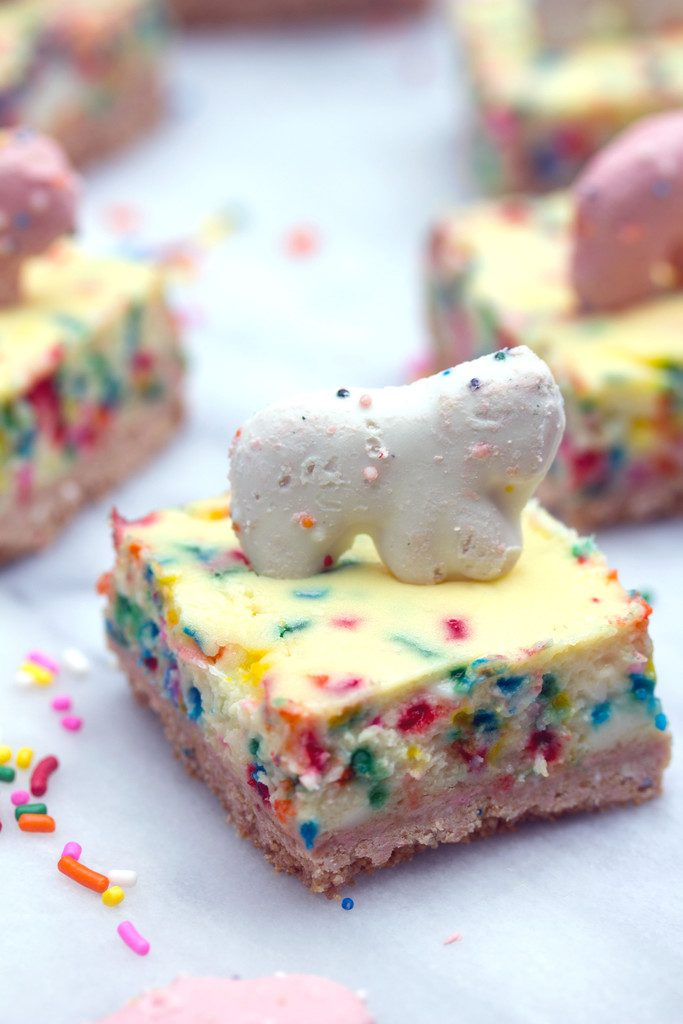 Frosted Animal Cracker Cheesecake Bars -- Funfetti cheesecake with a circus animal cookie crust! | wearenotmartha.com