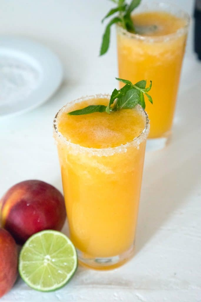 Overhead view of two glasses of bright orange frozen peach margarita topped with mint with a lime half, peaches, and a plate of salt in the background