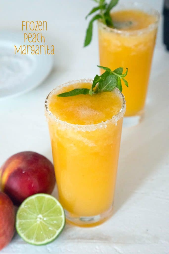 Overhead view of two glasses of bright orange frozen peach margarita topped with mint with a lime half, peaches, and a plate of salt in the background with recipe title at top