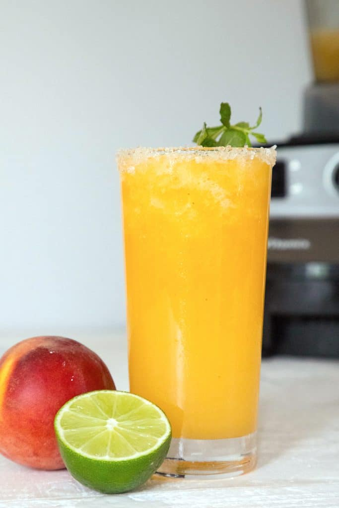 Head-on view of a tall bright orange glass or frozen peach margarita with a lime half and peach in front of it and a Vitamix blender in back