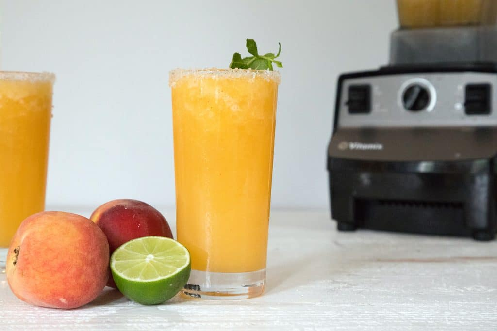 Landscape view photo of a tall glass of bright orange frozen peach margarita with a lime half, peaches, second margarita, and Vitamix blender in background
