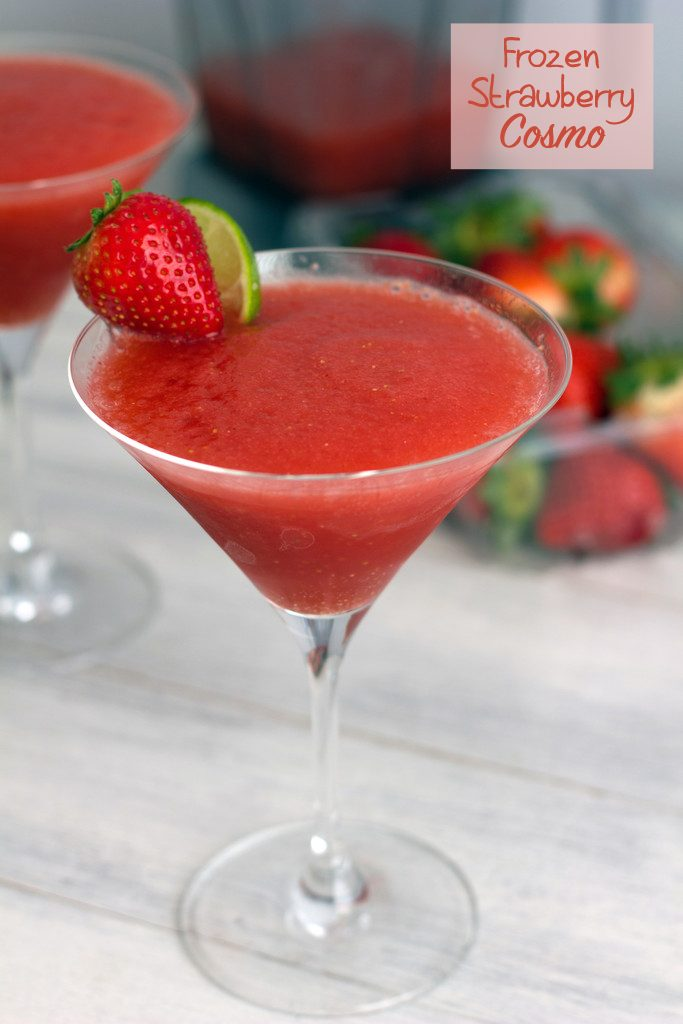 "Head-on view of frozen strawberry cosmo with strawberry lime garnish, another cosmo and strawberries in the background, and ""Frozen Strawberry Cosmo"" text at top"