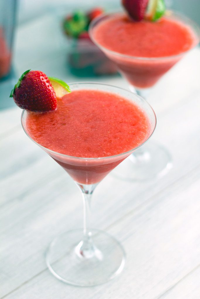 Head-on view of two frozen strawberry cosmos in martini glasses with strawberry and lime garnish
