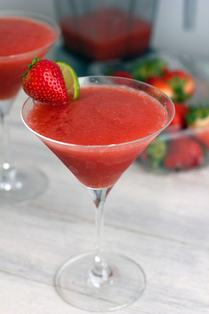 Head-on view of frozen strawberry cosmo with strawberry lime garnish, another cosmo and strawberries in the background