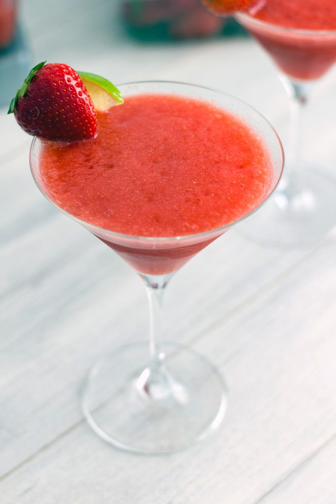 Close-up of a frozen strawberry cosmo in a martini glass with strawberry and lime garnish