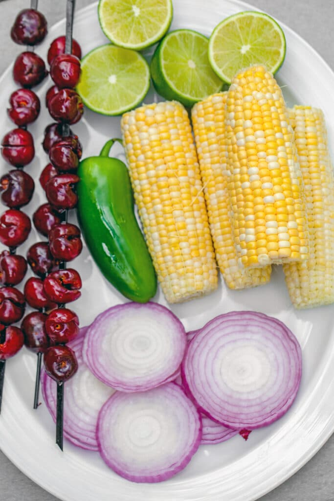 Overhead view of platter with corn on the cob, jalapeño, cherries on skewers, lime halves, and sliced red onions