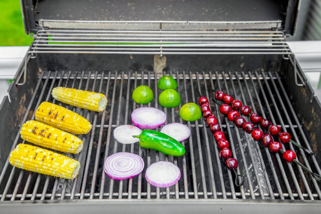Cherries, corn, red onion, jalapeño, and limes on grill