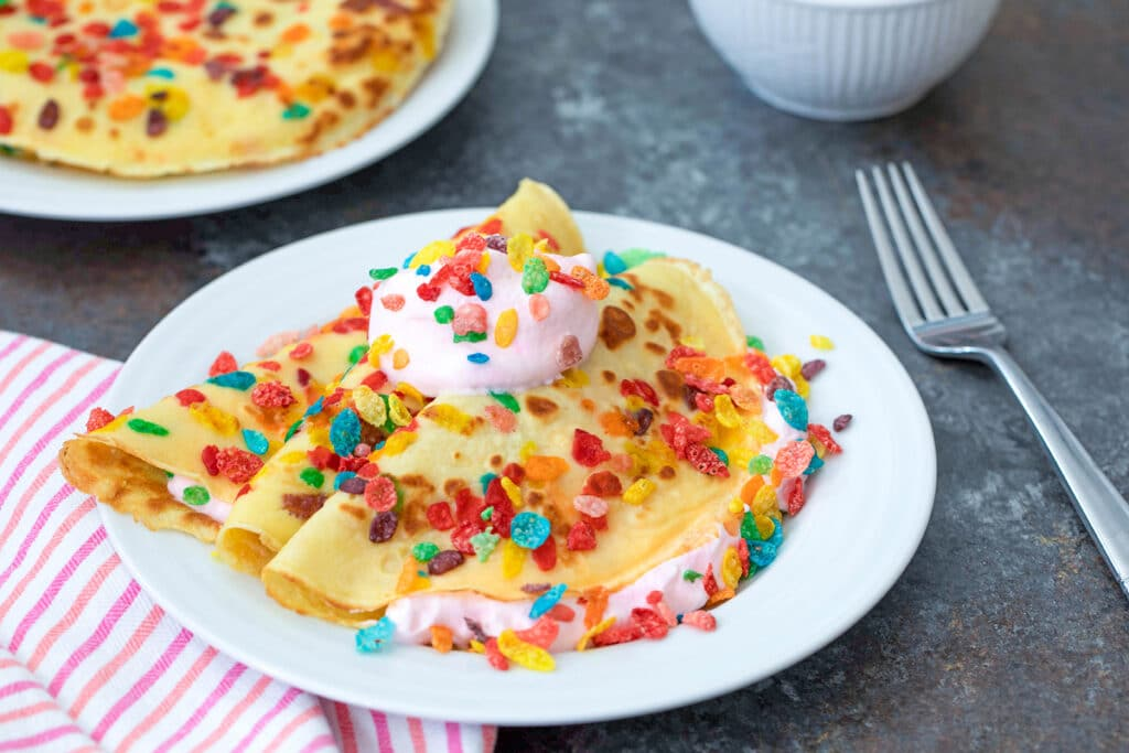 Head-on landscape view of white plate with Fruity Pebbles crepes with fork and second plate of crepes in background