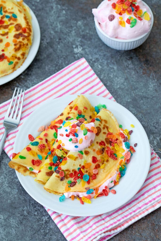 Fruity Pebbles crepes filled and topped with strawberry whipped cream on white plate with fork, bowl of whipped cream, and plate with more crepes in background