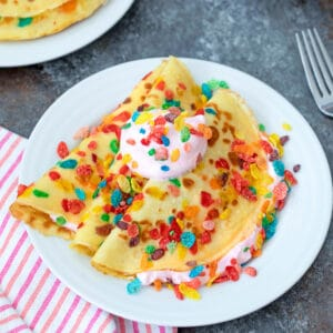 Fruity Pebbles Crepes -- Wake up to a fun and cheery breakfast of Fruity Pebbles Crepes with strawberry whipped cream. These crepes are easy to make and consist of a simple batter that can be prepared ahead of time to make morning breakfast a breeze   wearenotmartha.com #crepes #creperecipes #fruitypebbles #cereal #brunch #funbreakfasts