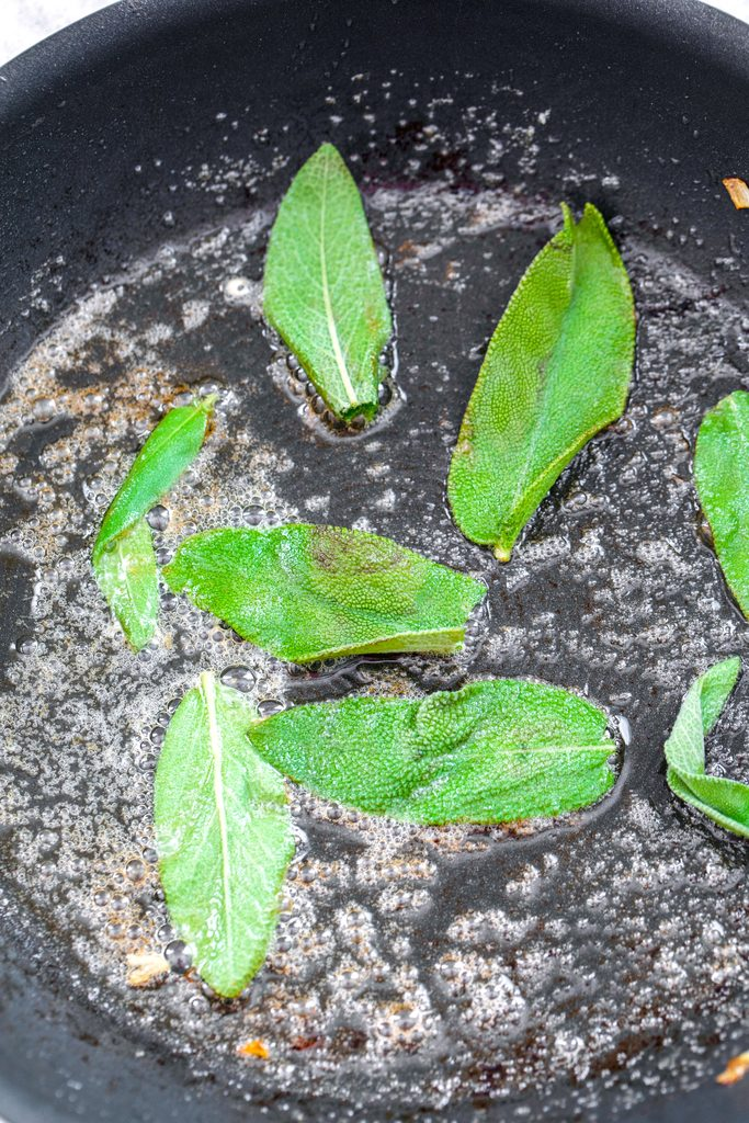 Overhead view of sage being fried in a skillet with shimmering oil