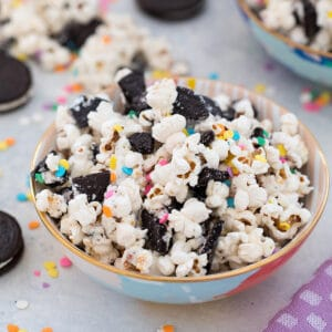 Head-on closeup view of Oreo funfetti popcorn with colorful sprinkles in a bowl with Oreo cookies and more popcorn and sprinkles in background