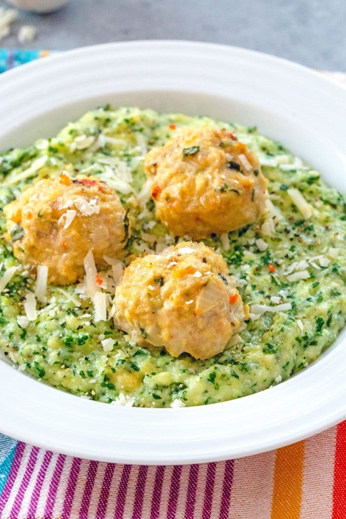 Head on view of white bowl filled with kale polenta and topped with three chicken meatballs on a colorful placemat
