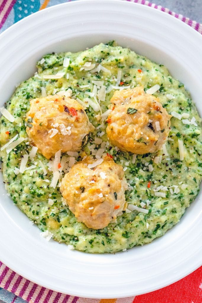 Overhead view of a white bowl filled with kale polenta and topped with three garlic habanero chicken meatballs
