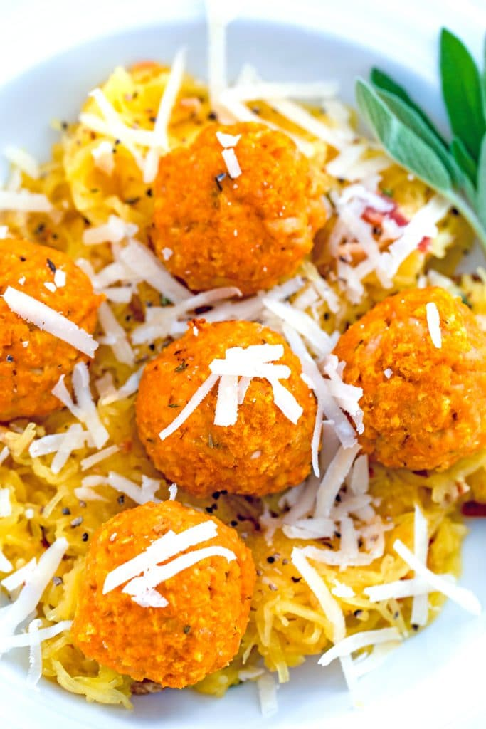 Close-up of pumpkin chicken meatballs topped with parmesan cheese over garlicky spaghetti squash with sage