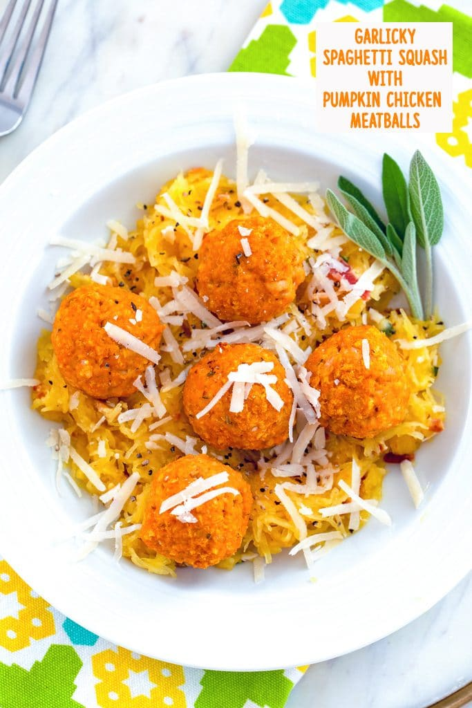 Overhead view of garlicky spaghetti squash in a white bowl with chicken pumpkin meatballs and parmesan cheese on top with sage and recipe title at the top
