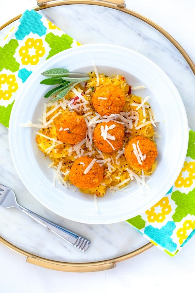 Bird's eye view of white bowl of garlicky spaghetti squash with pumpkin chicken meatballs with parmesan and sage on a marble surface with colorful napkin and fork