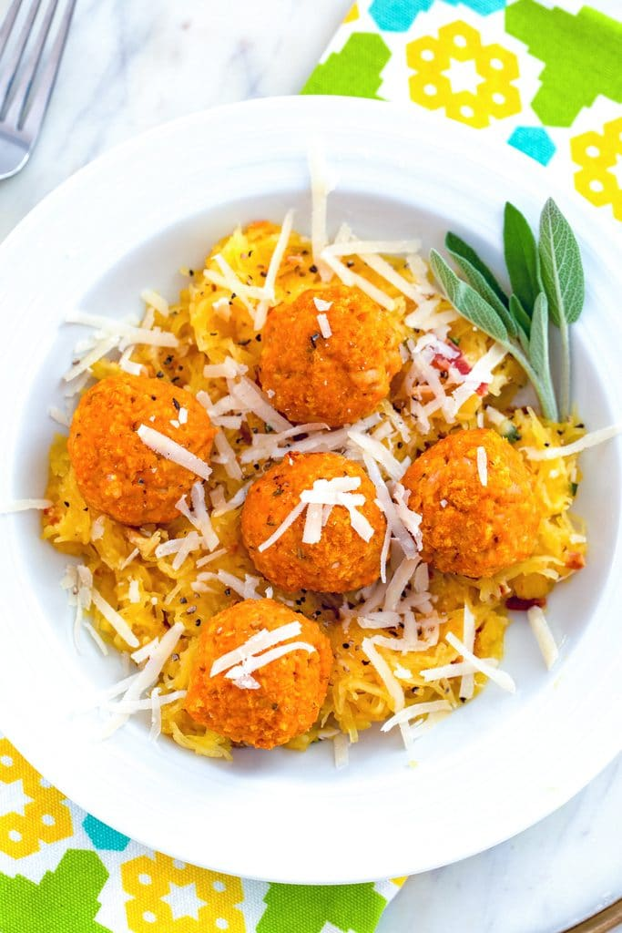 Overhead view of garlicky spaghetti squash in a white bowl with chicken pumpkin meatballs and parmesan cheese on top with sage
