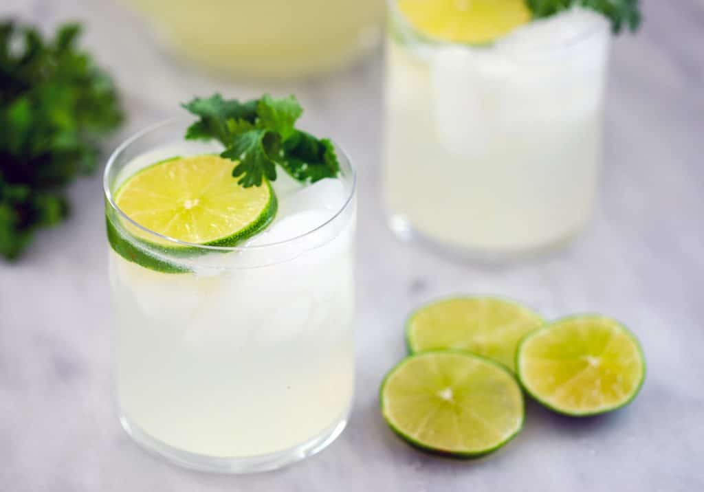 Landscape view of two gin lime rickeys with lime rounds and cilantro with additional lime rounds and a bunch of cilantro in the background