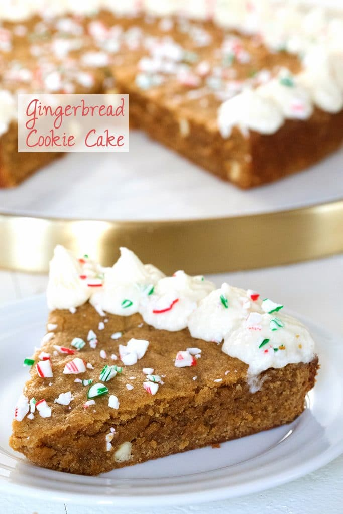 Head-on view of a thick slice of gingerbread cookie cake on a white plate with the rest of the cake in the background and recipe title on image