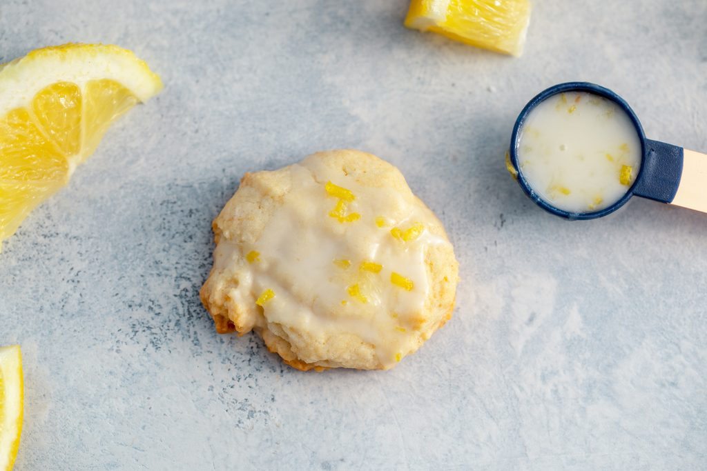 Landscape view of a glazed lemon cookie on a grey surface topped with lemon zest with lemon wedges and a teaspoon filled with lemon glaze