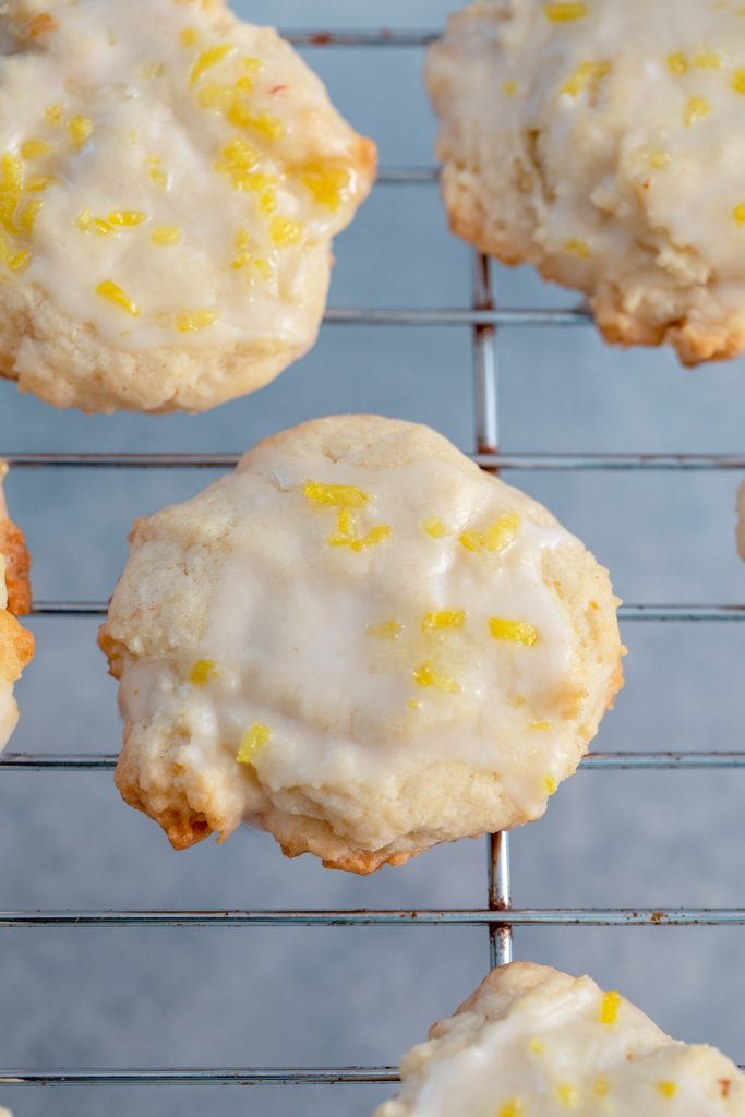 Glazed lemon cookies topped with lemon zest on a baking sheet