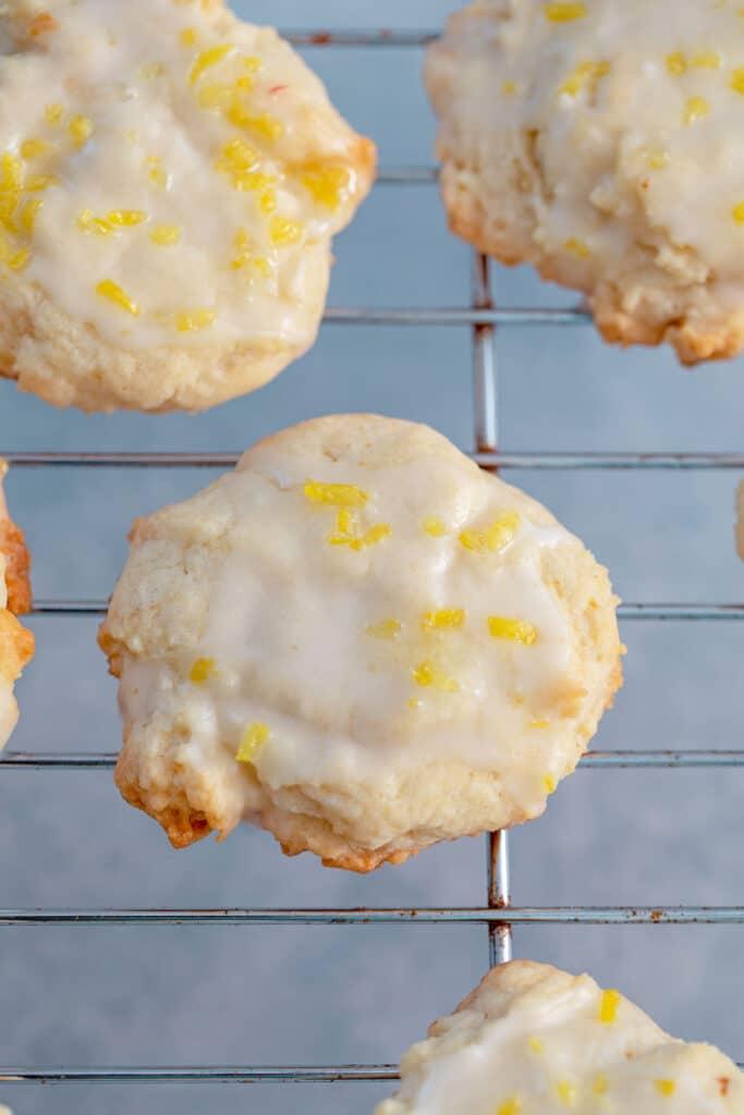Glazed lemon cookies topped with lemon zest on a baking sheet