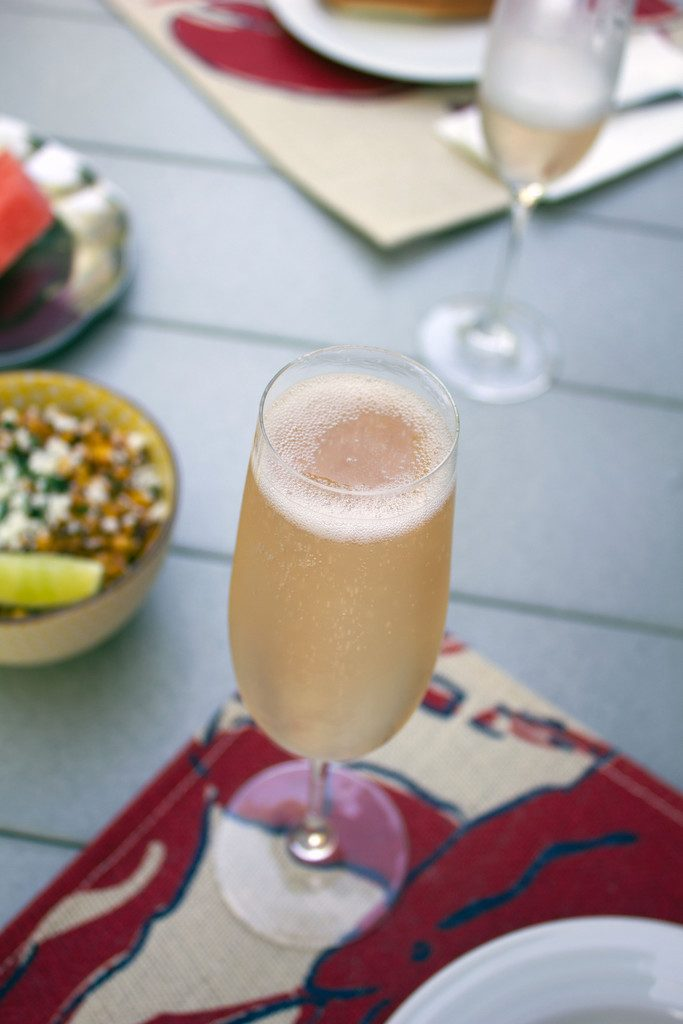 Glass of champagne on placemat on table with elote salad in the background