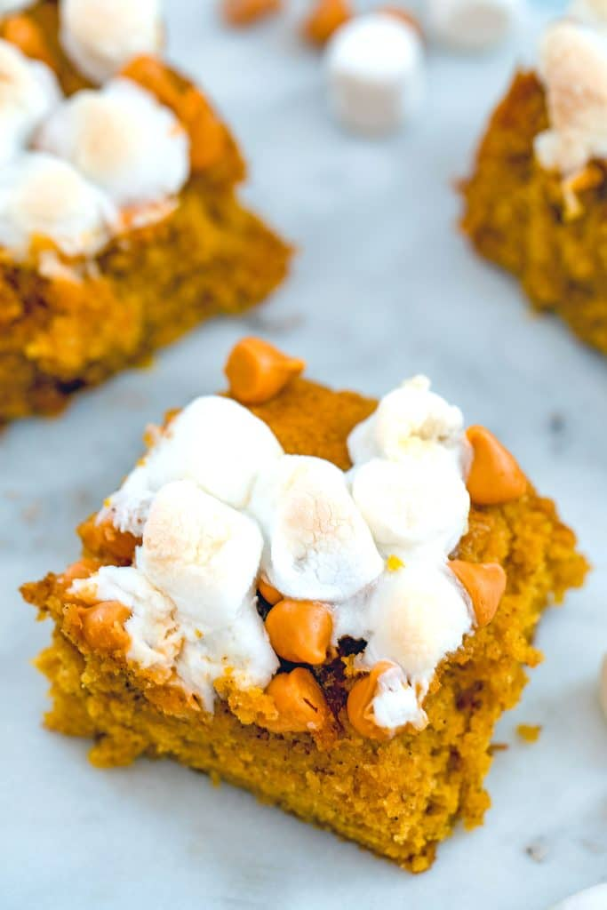 Overhead view of multiple pumpkin butterscotch blondies topped with marshmallows on a white surface