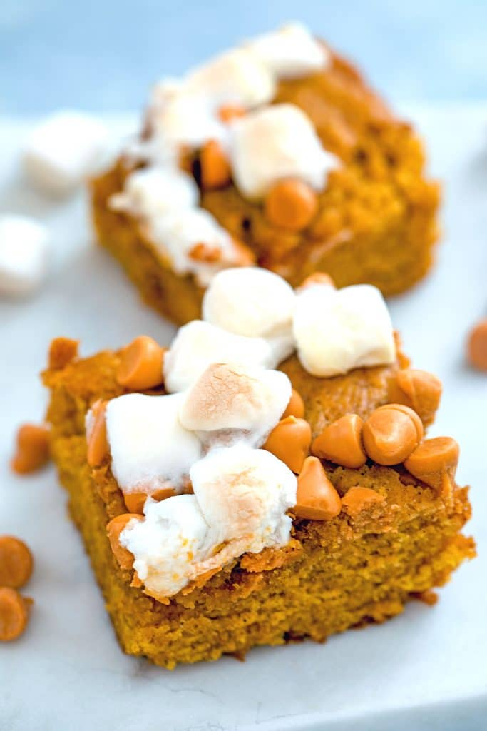 Close-up of two pumpkin butterscotch blondies topped with mini marshmallows on a white surface