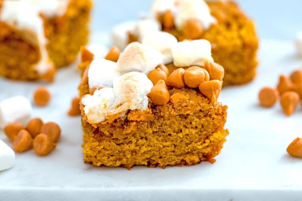 Landscape image featuring close-up view of a pumpkin butterscotch blondie on a white surface with mini marshmallows and butterscotch chips scattered around