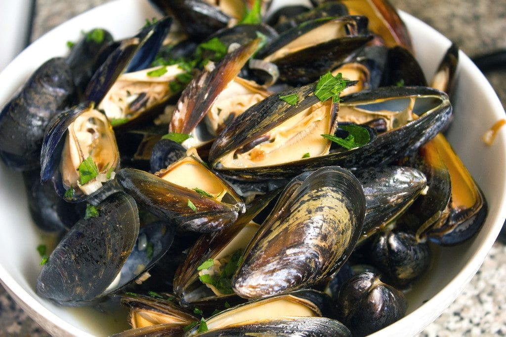 Landscape view of mussels in a white bowl, cooked  and topped with parsley