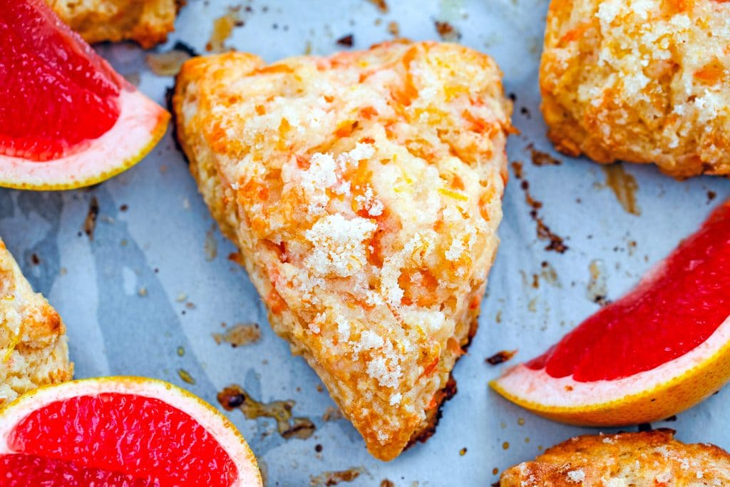 Landscape closeup view of grapefruit scone on a baking sheet with pink grapefruit segments and more scones around it