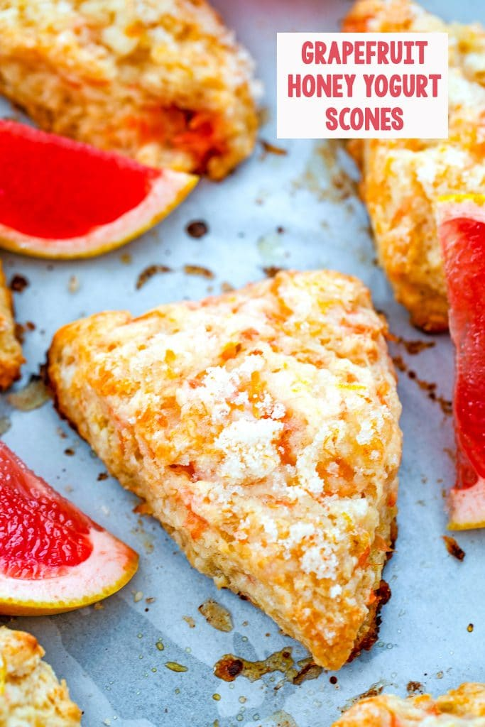 Overhead view of grapefruit scones on a baking sheet surrounded by pink grapefruit segments with the recipe title at top