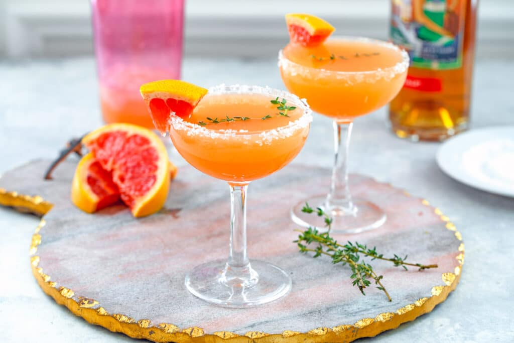 Landscape head-on view of two grapefruit lillet cocktails on a pink marble tray with grapefruit wedges, thyme sprigs, cocktail shaker, and bottle of Lillet in background