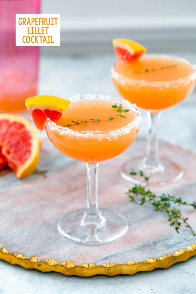Head-on view of a grapefruit lillet cocktail in coup glass with second cocktail, thyme sprigs, and grapefruit edges in background and recipe title at top