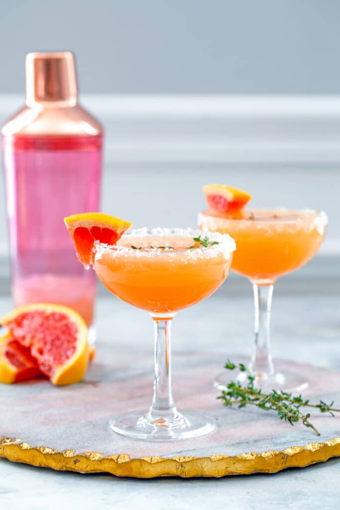 Head-on view of two grapefruit lillet cocktails with grapefruit wedges and cocktail shaker in background