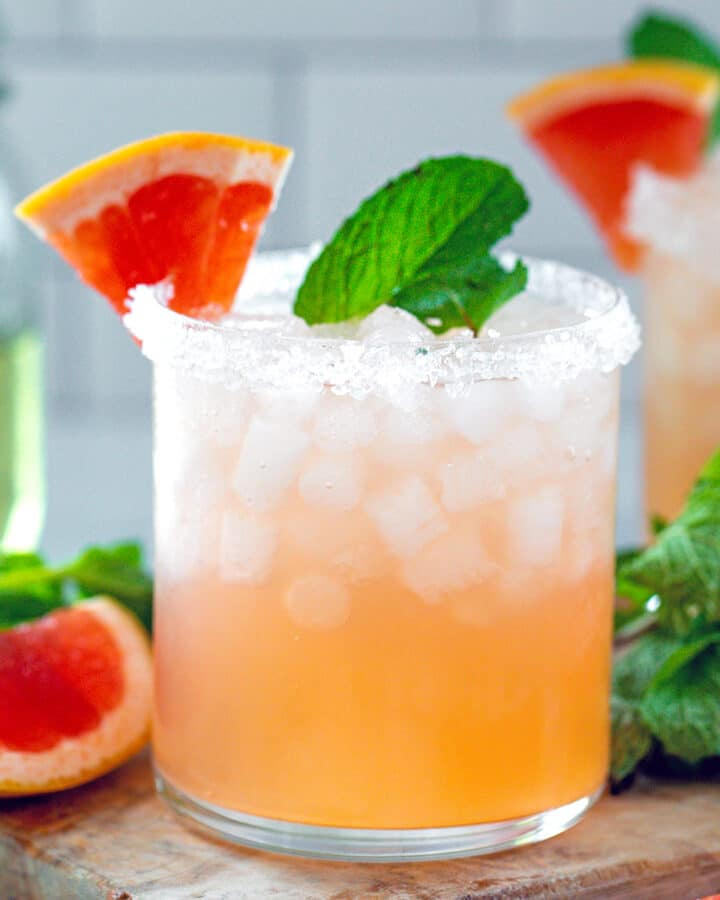 Head-on closeup view of a grapefruit mint margarita with fresh mint and grapefruit wedges all around