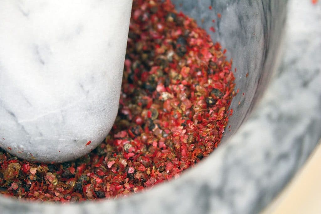 Pink peppercorns being crushed with a mortar and pestle