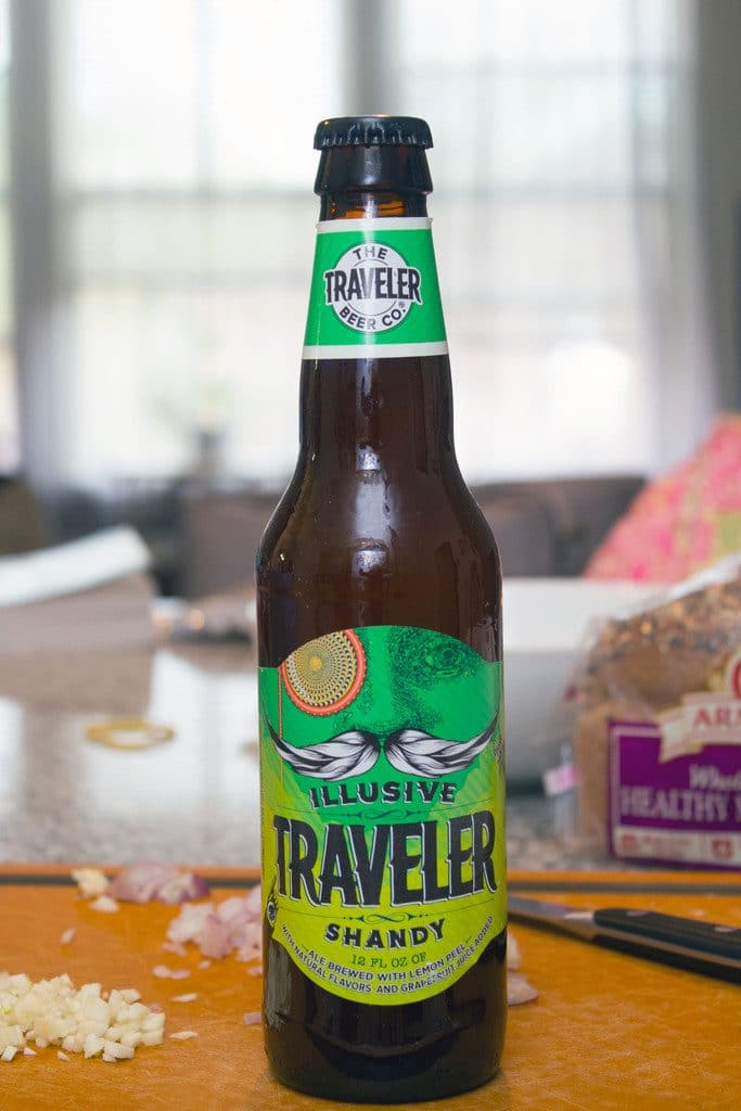 Head-on view of Illusive Traveler Grapefruit Shandy beer bottle on a cutting board
