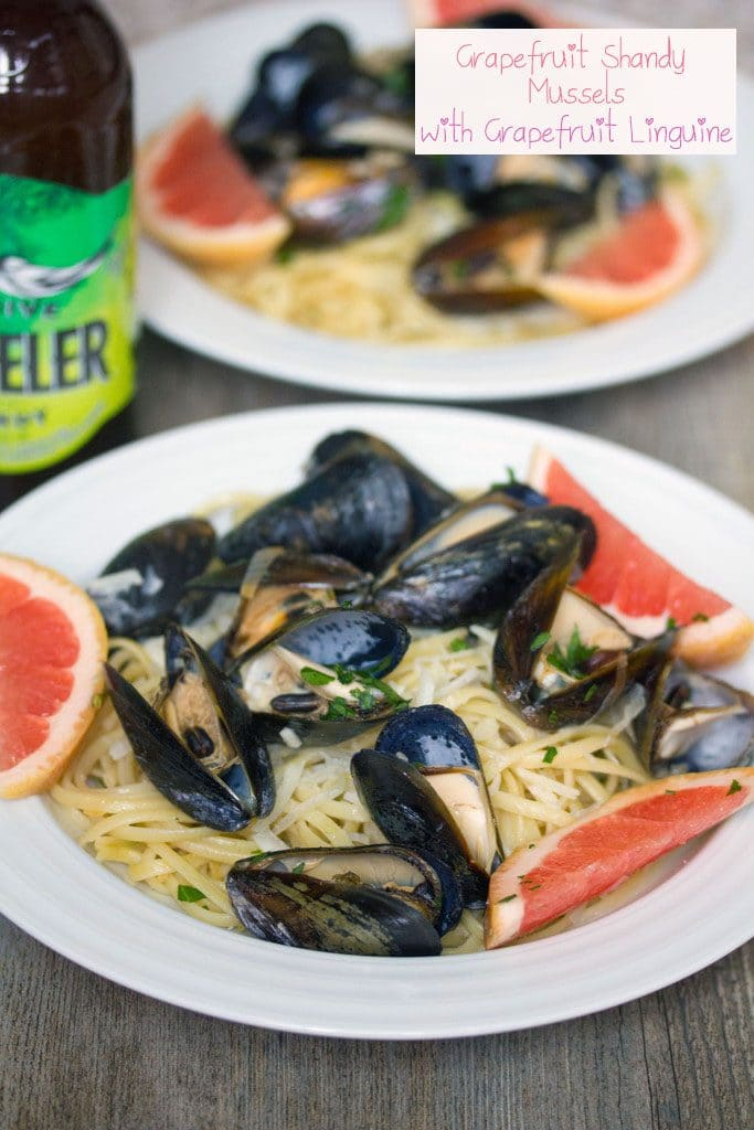 Head-on view of a white bowl of grapefruit shandy mussels over linguine with grapefruit slice garnishes, second bowl in the background, bottle of beer, and recipe title at top