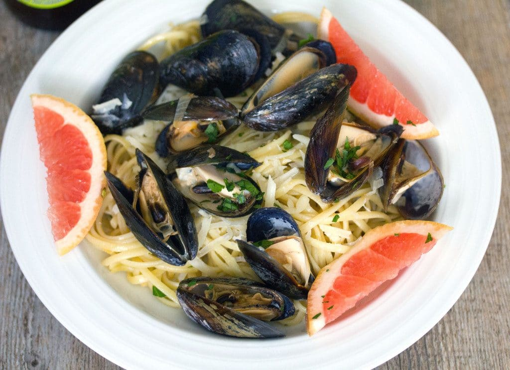 Landscape overhead view of grapefruit shandy mussels over linguine with grapefruit wedges in a white bowl