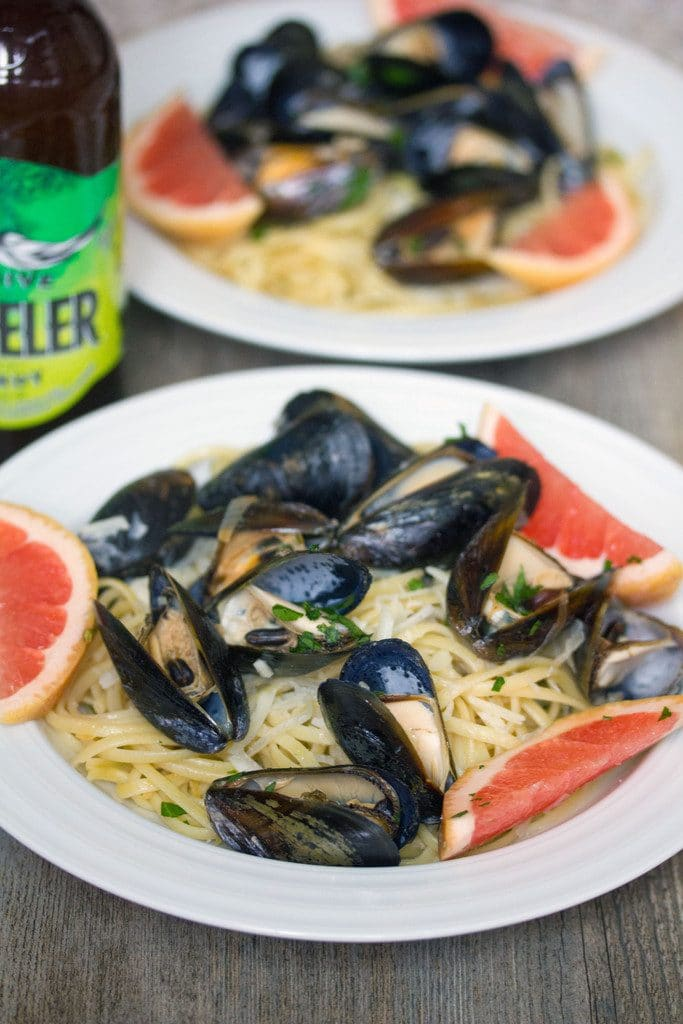 Head-on view of a white bowl of grapefruit shandy mussels over linguine with grapefruit slice garnishes, second bowl in the background, and bottle of beer